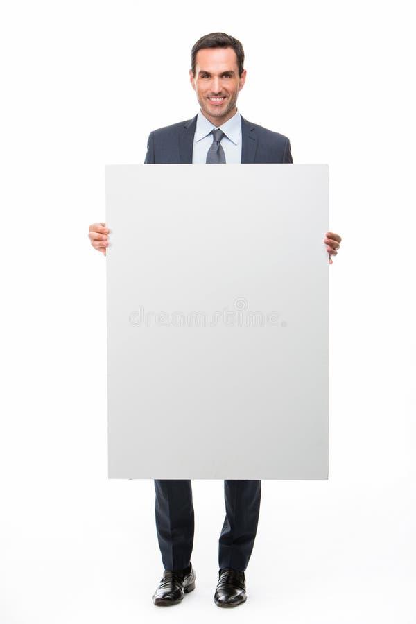 Hombre de negocios que lleva a cabo un cartel blanco imagenes de archivo