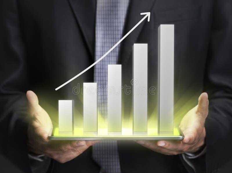 Hombre de negocios que lleva a cabo un gráfico que muestra crecimiento imagenes de archivo