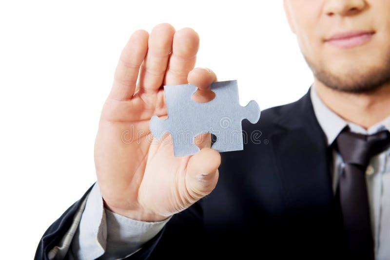 Hombre de negocios que lleva a cabo un rompecabezas fotos de archivo