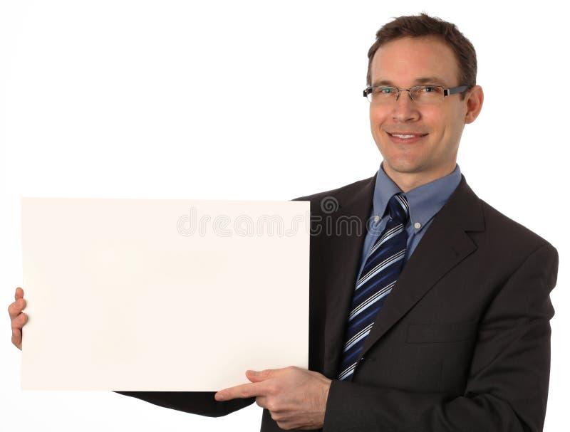 Hombre de negocios que lleva a cabo una muestra en blanco imagen de archivo libre de regalías