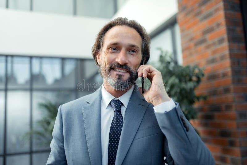 Hombre de negocios que lleva el lazo elegante que sonríe mientras que recibe llamada de teléfono foto de archivo libre de regalías