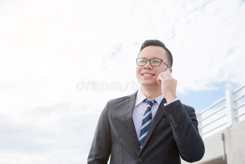 Hombre de negocios que lleva el traje negro que sonríe mientras que habla vía el teléfono móvil imagen de archivo