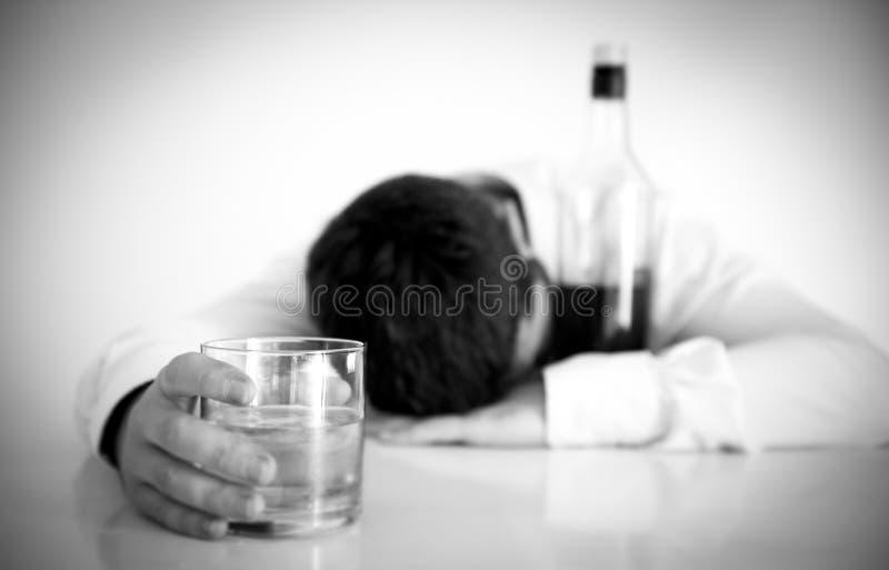 Hombre de negocios que lleva la camisa azul bebida en el escritorio en el fondo blanco fotografía de archivo