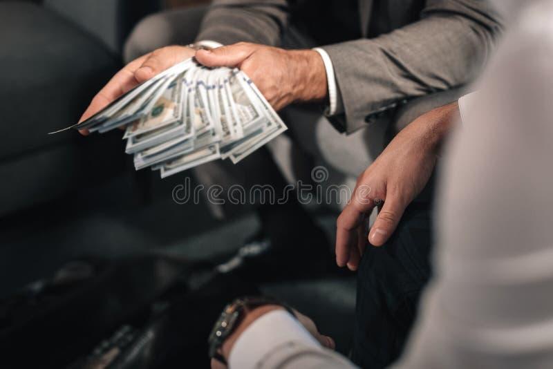 Hombre de negocios que lleva la chaqueta gris oscuro que da el soborno al abogado fotos de archivo libres de regalías