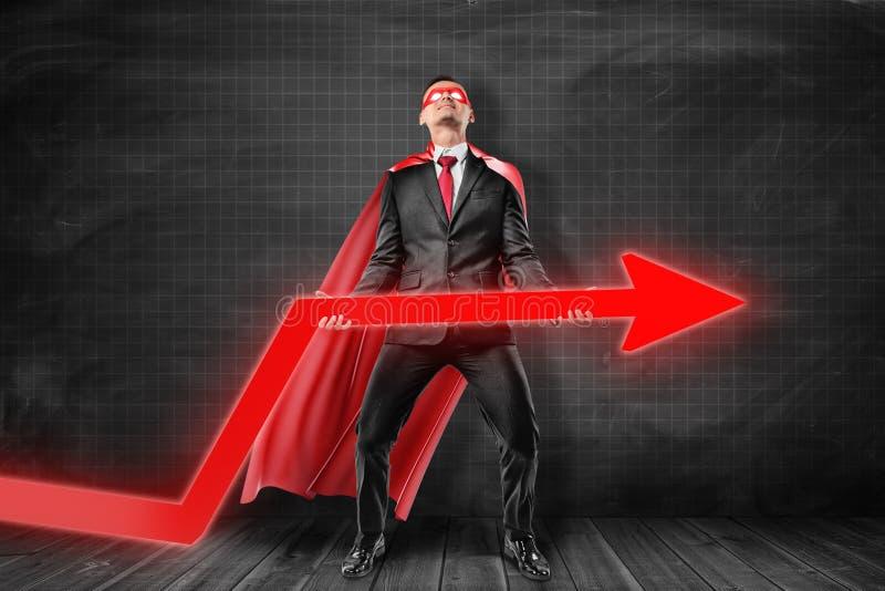 Hombre de negocios que lleva la máscara roja del superhombre y capa que sostiene la flecha roja del diagrama en fondo negro libre illustration
