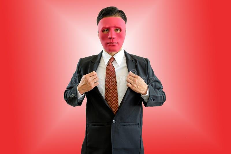 Hombre de negocios que lleva la máscara roja en fondo rojo con la trayectoria de recortes fotografía de archivo