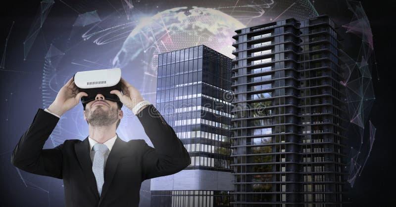 Hombre de negocios que lleva las auriculares de la realidad virtual con los edificios altos con el campo enérgico del globo del m fotografía de archivo libre de regalías