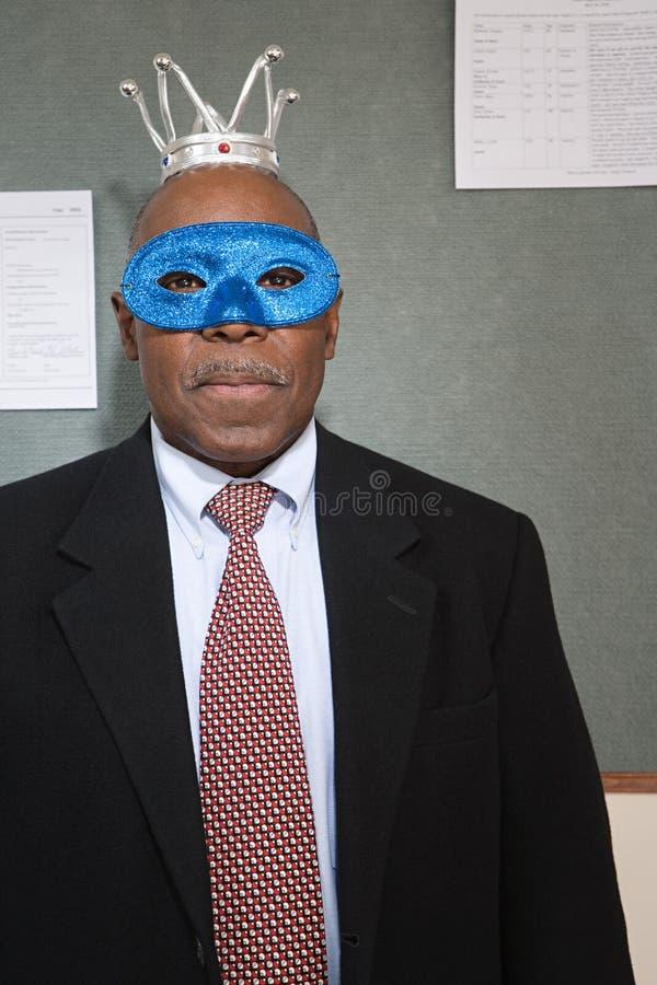 Hombre de negocios que lleva una corona y una máscara imagen de archivo libre de regalías