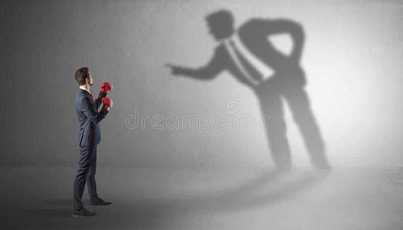 Hombre de negocios que lucha con su sombra mandona imagen de archivo