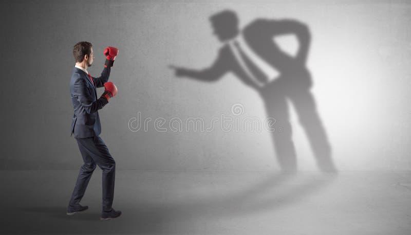 Hombre de negocios que lucha con su sombra mandona foto de archivo libre de regalías
