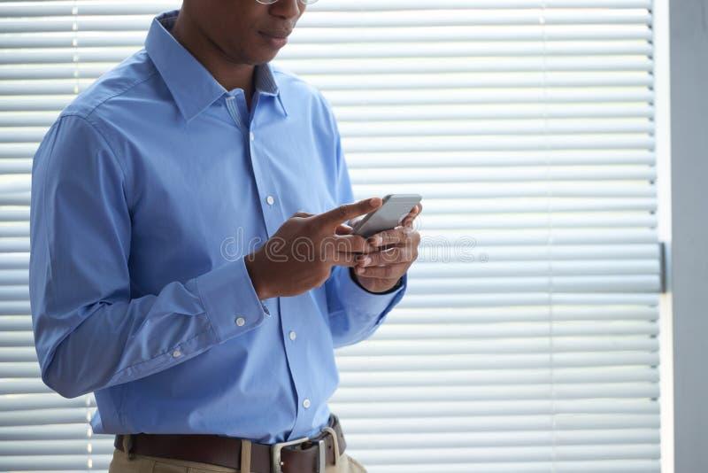 Hombre de negocios que manda un SMS fotografía de archivo libre de regalías