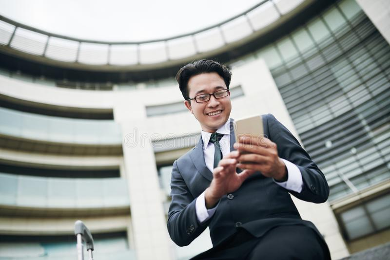 Hombre de negocios que manda un SMS en aeropuerto imagen de archivo libre de regalías