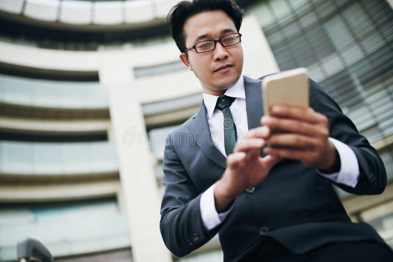 Hombre de negocios que manda un SMS en smartphone fotos de archivo libres de regalías