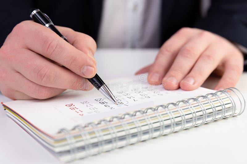 Hombre de negocios que marca una fecha en un calendario en un traje azul marino imagen de archivo libre de regalías
