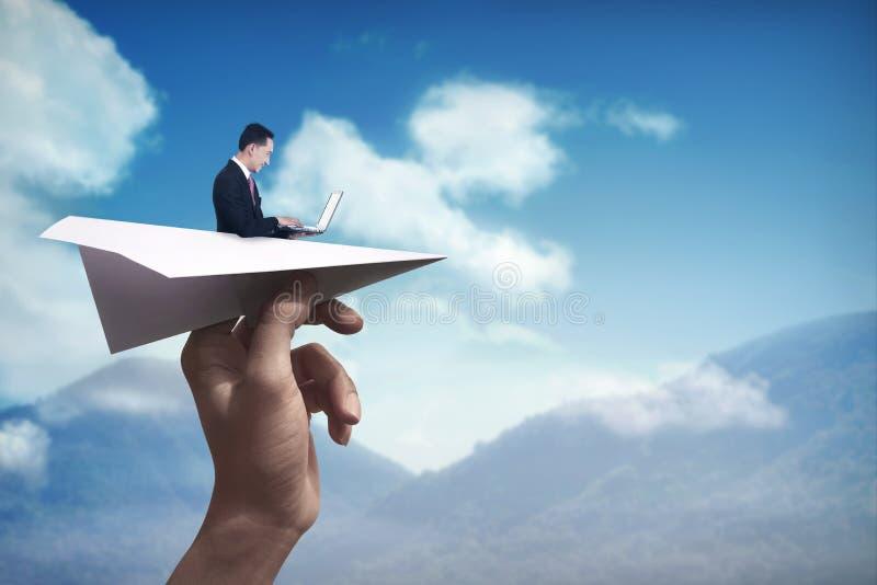 Hombre de negocios que mecanografía con el ordenador portátil en el avión de papel fotos de archivo libres de regalías