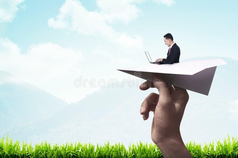 Hombre de negocios que mecanografía con el ordenador portátil en el avión de papel imagenes de archivo