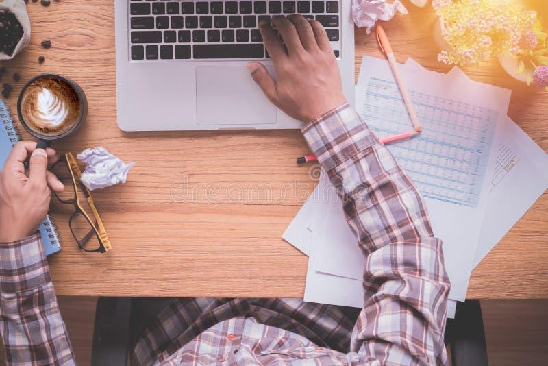 Hombre de negocios que mecanografía en el teclado del cuaderno y el café de consumición en la tabla de madera de la oficina imagenes de archivo
