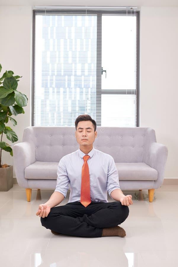 Hombre de negocios que medita en actitud del loto en el piso en la oficina imagen de archivo