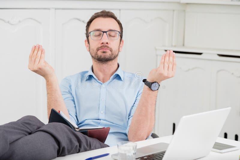 Hombre de negocios que medita en la oficina con sus piernas en el escritorio imágenes de archivo libres de regalías