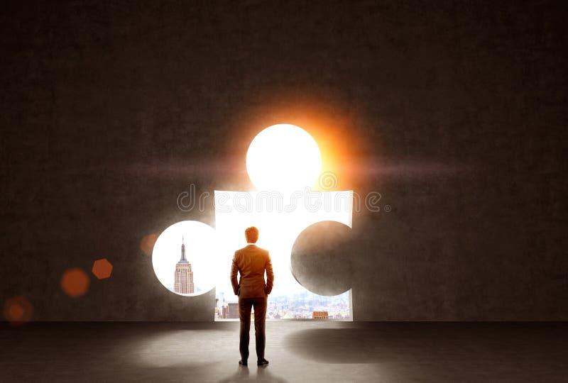 Hombre de negocios que mira el agujero del rompecabezas foto de archivo libre de regalías