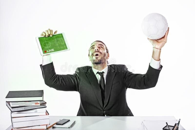 Hombre de negocios que mira el juego en línea en el trabajo foto de archivo