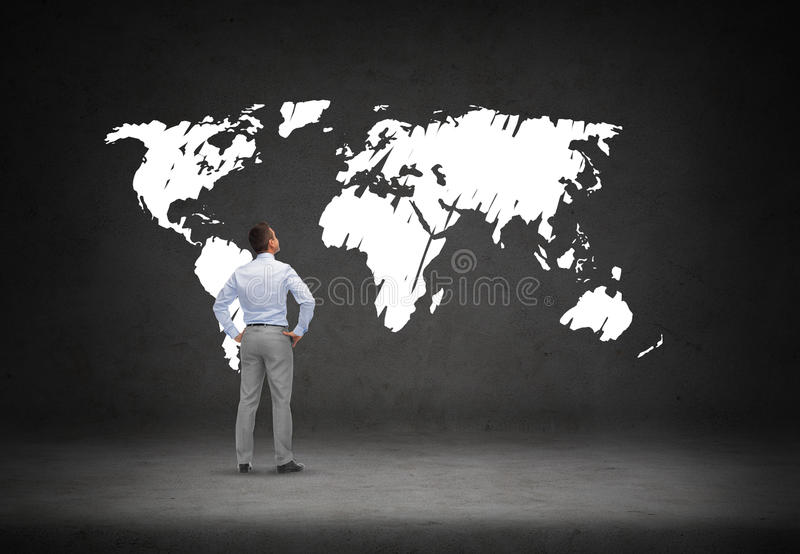 Hombre de negocios que mira el mapa del mundo fotos de archivo