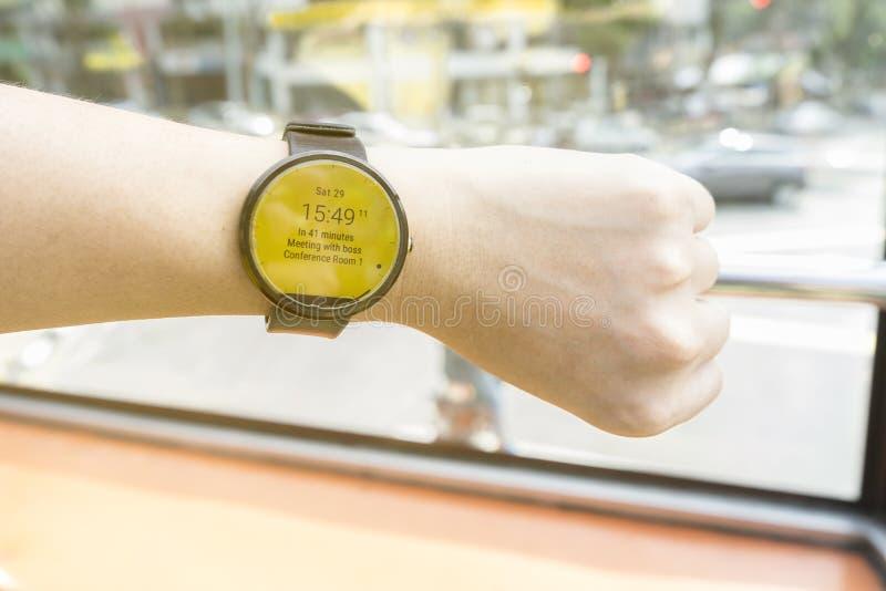 Hombre de negocios que mira el smartwatch para comprobar la época del encuentro fotografía de archivo libre de regalías