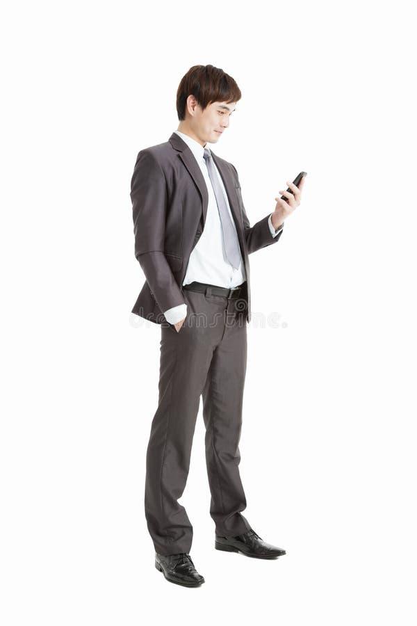 Hombre de negocios que mira el teléfono elegante imagen de archivo