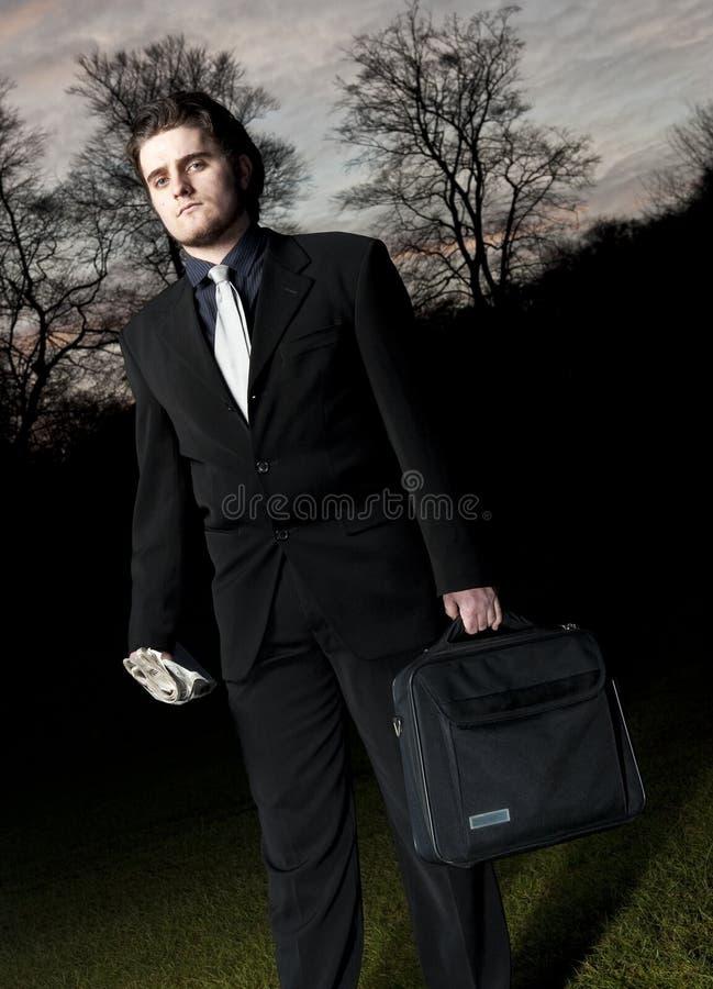 Hombre de negocios que mira en cámara, mientras que puesta del sol. foto de archivo libre de regalías