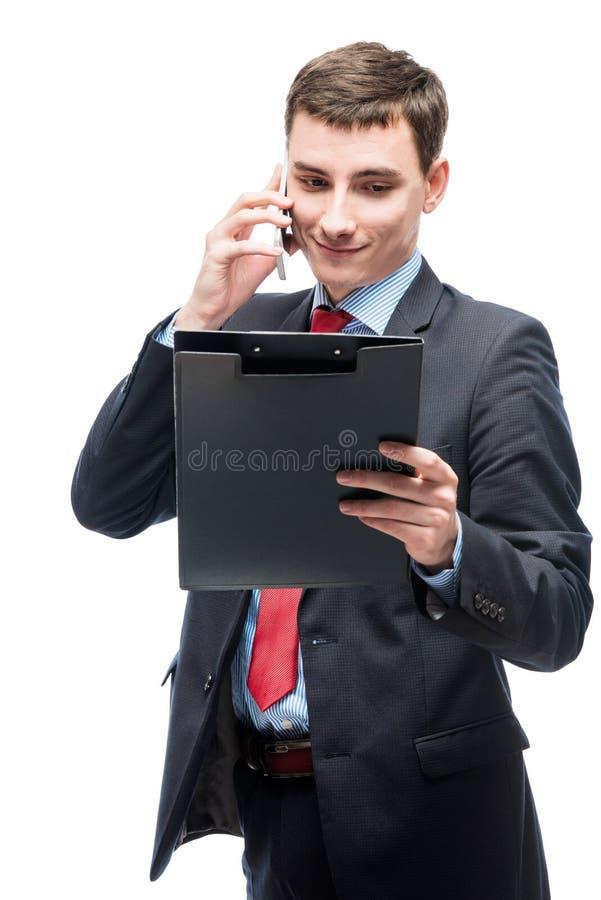 Hombre de negocios que mira en una carpeta y que habla en el teléfono imagen de archivo libre de regalías