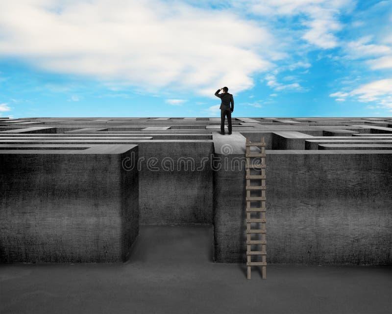 Hombre de negocios que mira encima de la pared concreta del laberinto con la escalera imagen de archivo libre de regalías