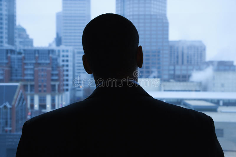 Hombre de negocios que mira fuera de ventana imagenes de archivo