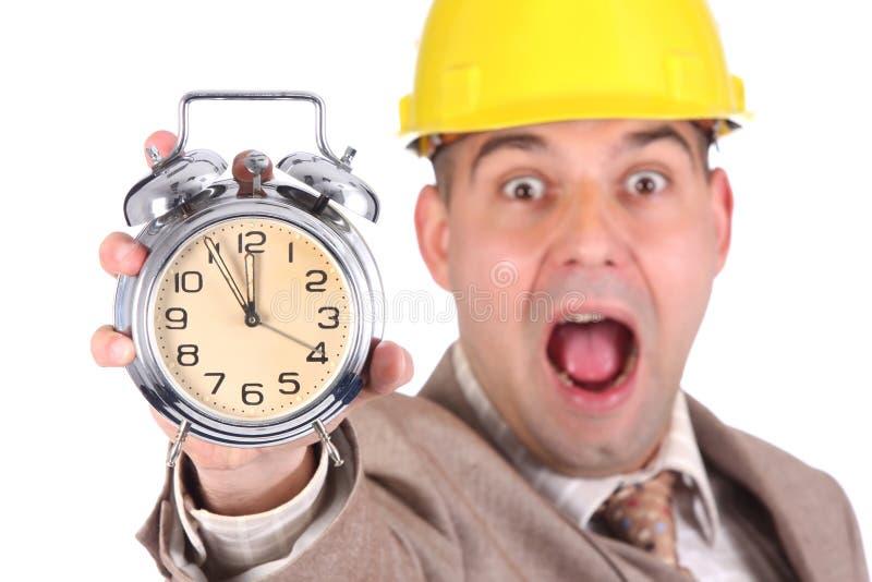 Hombre de negocios que mira la alarma del reloj foto de archivo