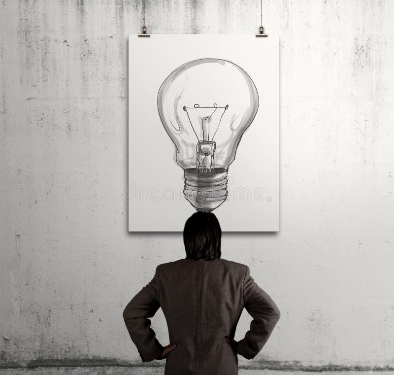 Hombre de negocios que mira la bombilla en marco del arte fotografía de archivo libre de regalías
