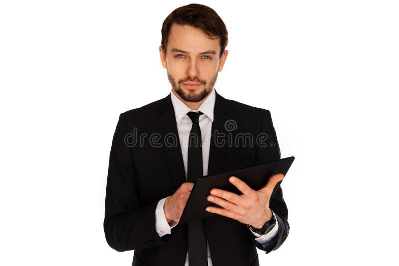 Hombre de negocios que mira a la cámara como él información que mecanografía sobre la tableta-PC foto de archivo libre de regalías