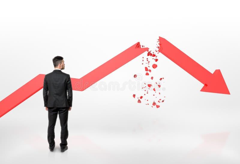Hombre de negocios que mira la flecha rota roja del gráfico que cae aislada en el fondo blanco imagenes de archivo