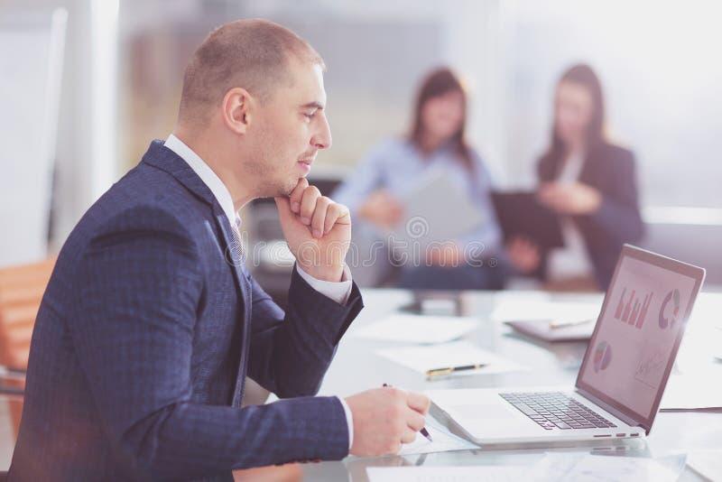 Hombre de negocios que mira la pantalla del ordenador portátil con las cartas financieras imagen de archivo libre de regalías