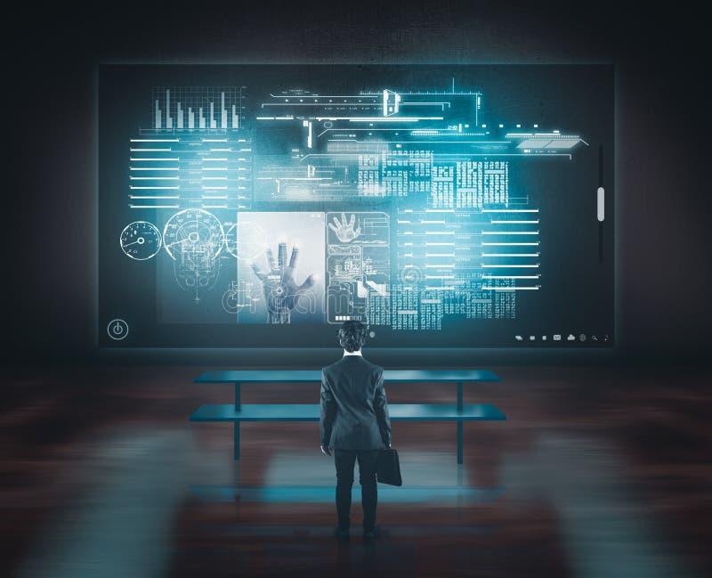 Hombre de negocios que mira la pantalla táctil grande sobre el escritorio imagen de archivo