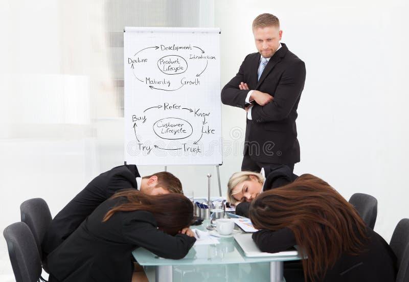 Hombre de negocios que mira a los colegas que duermen durante la presentación imagenes de archivo