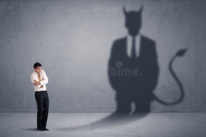 Hombre de negocios que mira su propio concepto de la sombra del demonio del diablo imagen de archivo libre de regalías