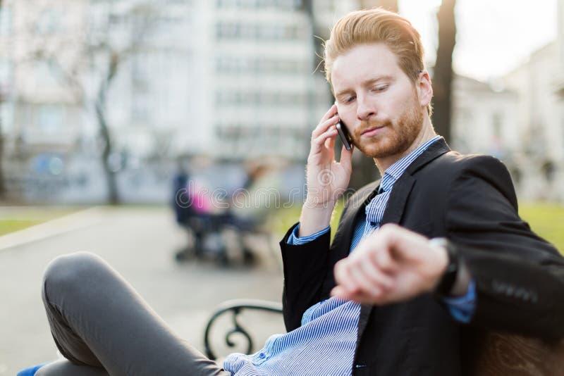 Hombre de negocios que mira su reloj en un día soleado en un parque de la ciudad fotos de archivo