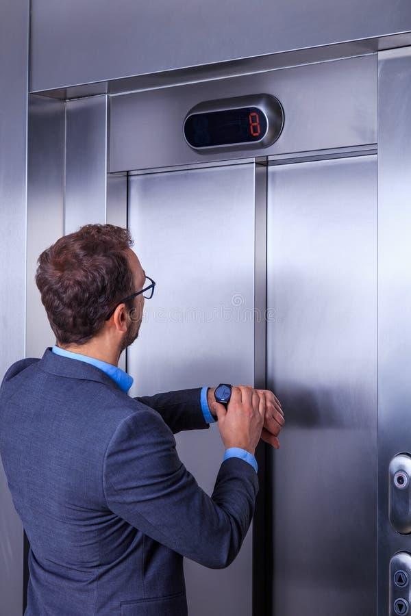 Hombre de negocios que mira su reloj mientras que espera el elevador fotografía de archivo libre de regalías