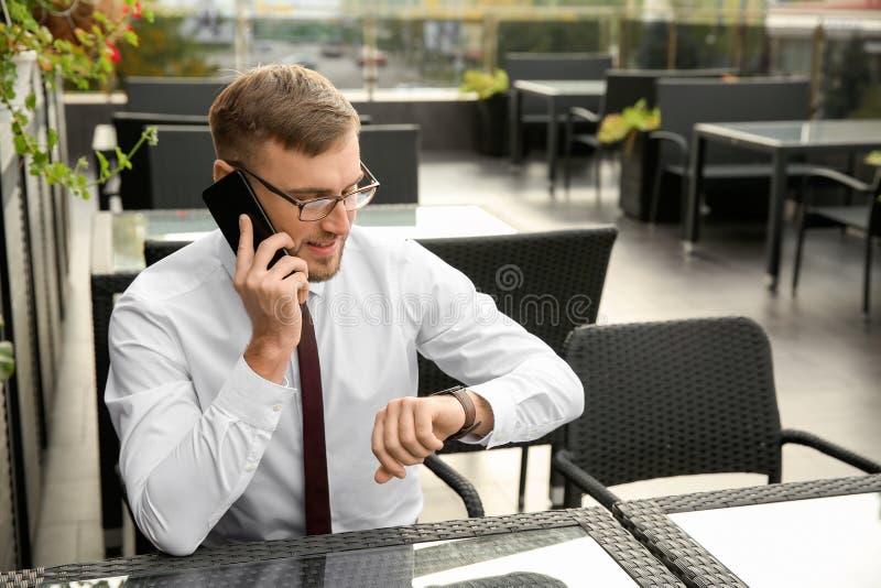 Hombre de negocios que mira su reloj mientras que habla por el teléfono en café fotografía de archivo