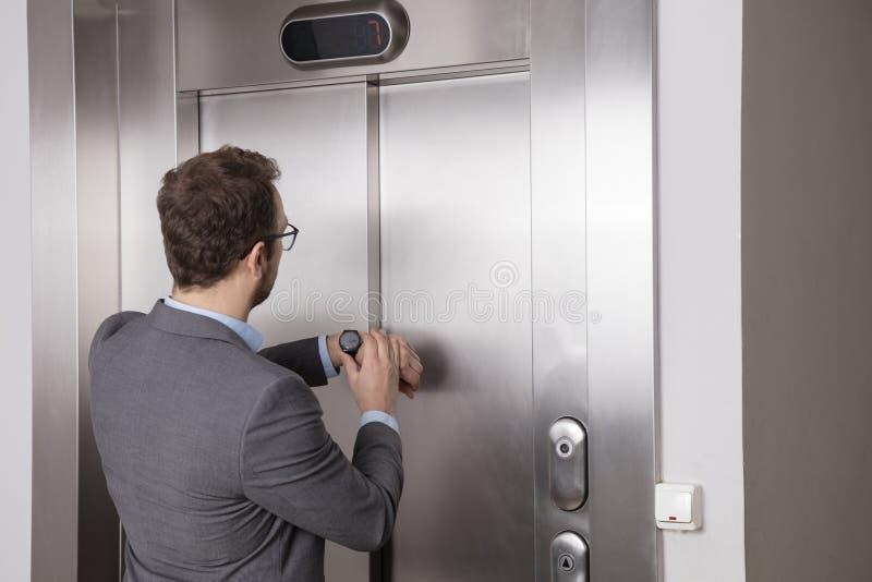 Hombre de negocios que mira su reloj mientras que espera el elevador imagen de archivo