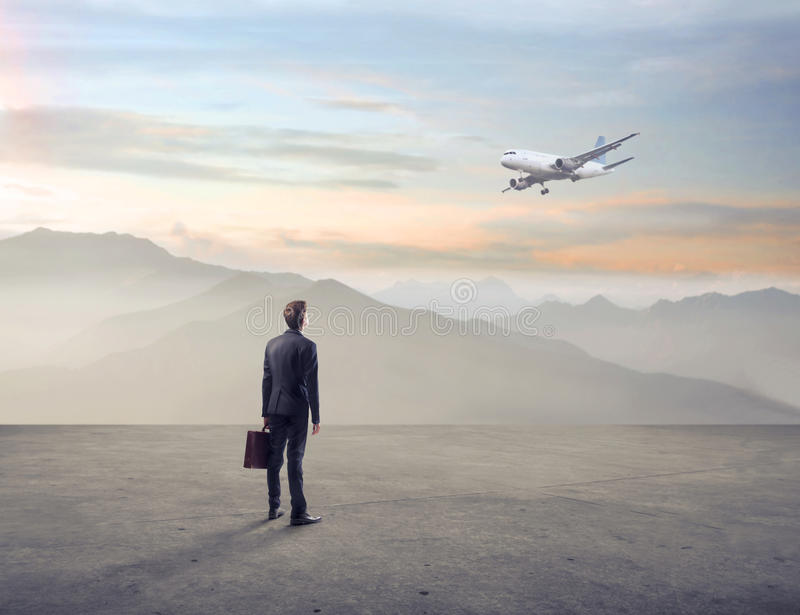 Hombre de negocios que mira un aeroplano en una tierra imágenes de archivo libres de regalías
