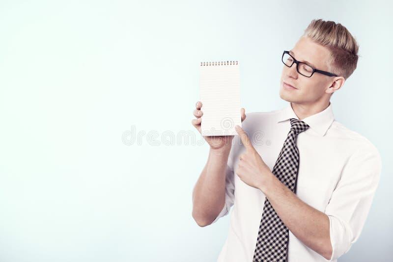 Hombre de negocios que mira y que señala el dedo la libreta vacía. fotos de archivo libres de regalías