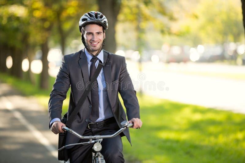 Hombre de negocios que monta una bicicleta para trabajar, conce de los ahorros del gas del concepto fotografía de archivo