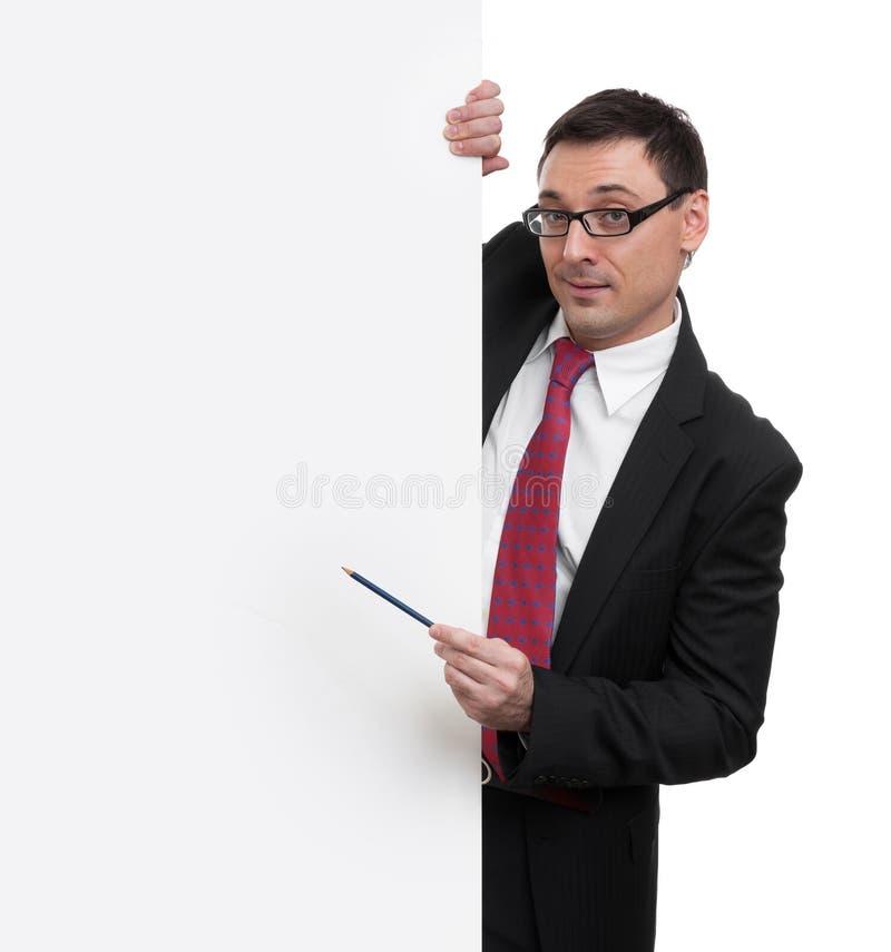 Hombre de negocios que muestra con el indicador al cartel en blanco foto de archivo