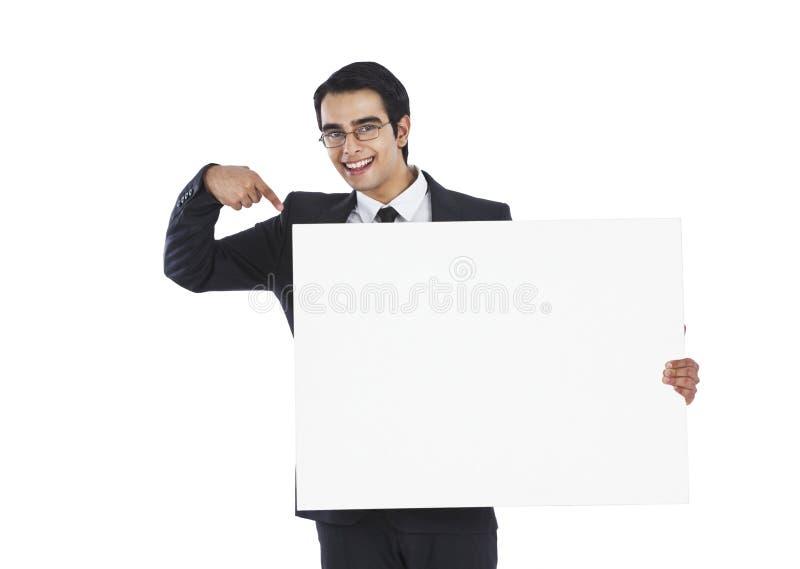 Hombre de negocios que muestra el cartel en blanco imagen de archivo
