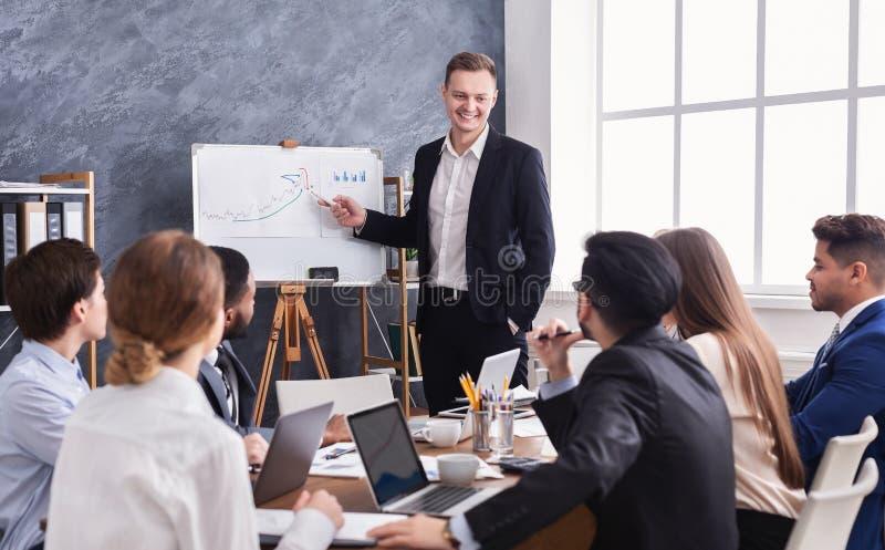 Hombre de negocios que muestra el diagrama durante la presentación imagen de archivo